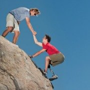 Young man with prosthetic leg being helped up a rock