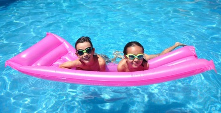 Two girls floating on a pink float in a swimming pool
