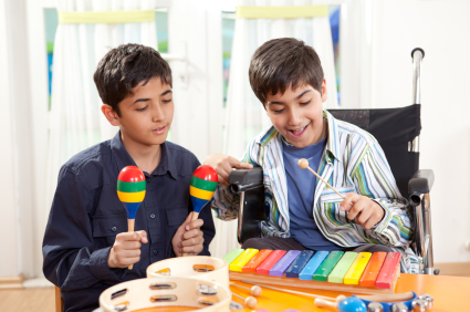 Family Fund.  Young carer helping his brother play music