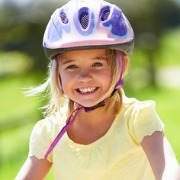 young girl wearing a cycle helmet on a bike