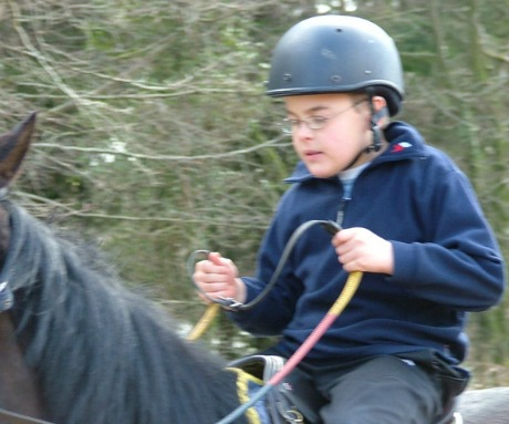 Disabled child with Cerebral Palsy horse riding at the Calvert Trust, Exmoor in Devon