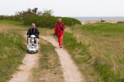 elderly man on a mobility scooter riding along a footpath
