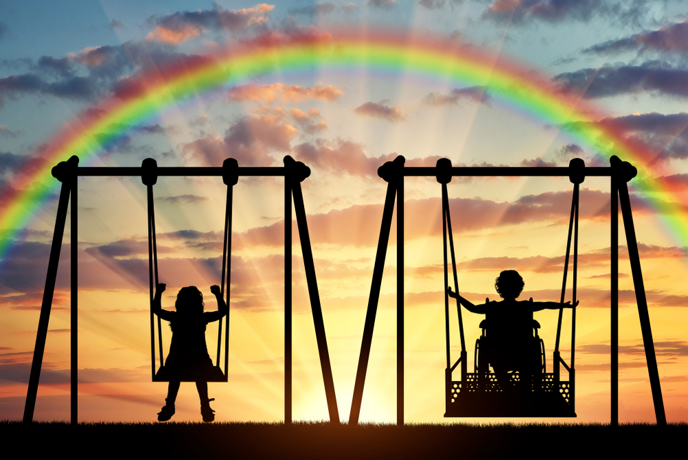Two children on swings.  One on a wheelchair swing.