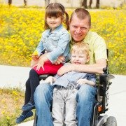 Disabled father in wheelchair with his two children