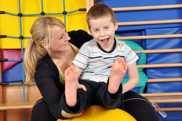 Disabled child with therapist on a physio ball
