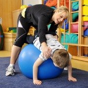 Disabled child with therapist being stretched over a physio ball