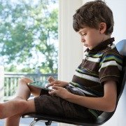 young man sat in chair using a tablet or ipad