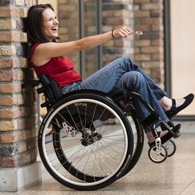 woman in manual wheelchair  being lent against the wall